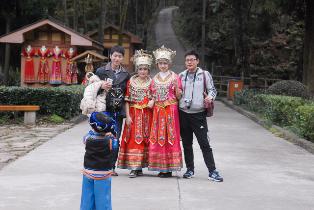 Chinese tourists with women in costume and child taking photo at Zhangjiejia., travelling in China independently