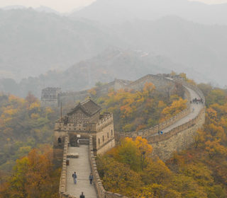 Great Wall with autumn trees and misty mountains.