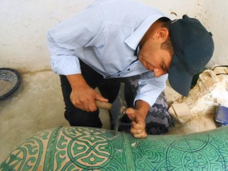 Artisan chipping an Islamic pattern into a vase