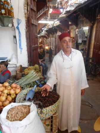 A traditionally dressed guide explains food in the souq Moroccan City Fez
